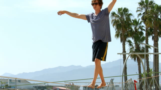 Slackliner walker balancing on tightrope in Santa Monica Beach, Los Angeles, California, 4K, from RAW file