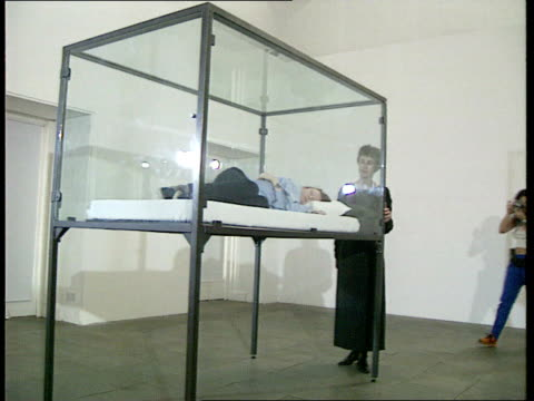 London Kensington Serpentine Gallery INT Tilda Swinton asleep in glass case as part of exhibit called 'The Maybe' Cornelia Parker looking at Swinton...