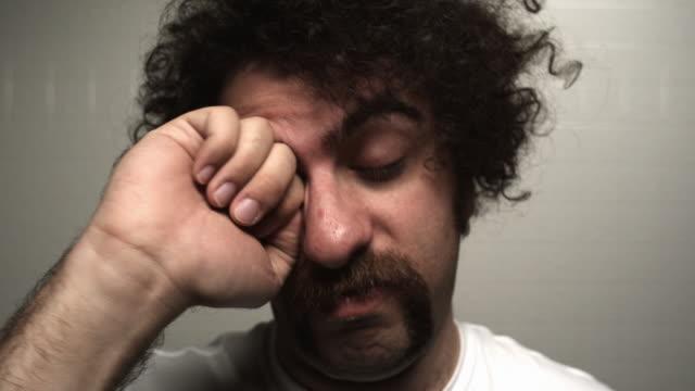 CU sleepy young man looking at camera and rubbing eyes, trying to wake up / Atlanta, Georgia