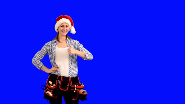 slender young woman construction worker in a cap of Santa Claus shows a copy space  on a blue background