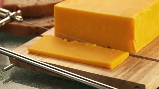 CU Slice being cut from block of cheddar cheese / Los Angeles, California, United States