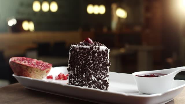 Bit av Schwarzwald tårta med granatäpple och körsbär toppning på tallrik