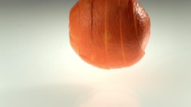 Slice of orange falling into water