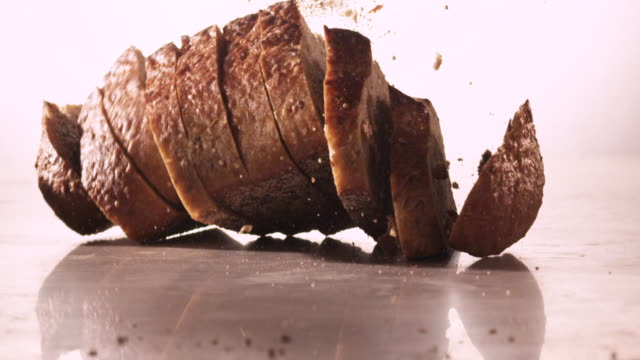 CU SLO MO Sliced loaf of bread falls onto surface resulting in bread flying everywhere / Los Angeles, California, United States