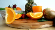 Slices Of Orange Drops Onto Cutting Board