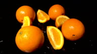 Slices Of Orange Falling On Black Background