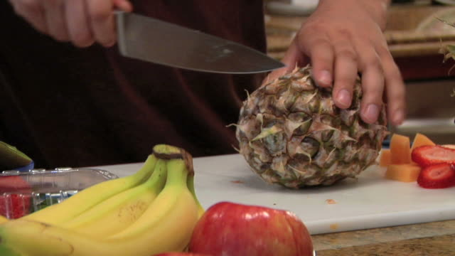 slicing a pineapple