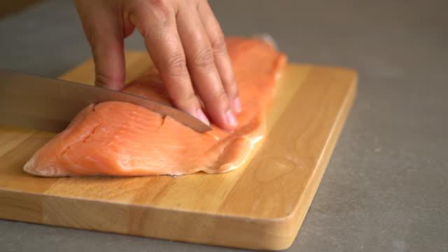 slicing salmon on wood board