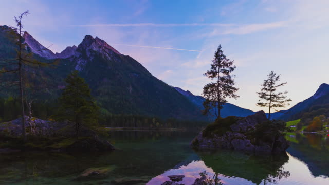 T/L PAN & Slider day to night transition at lake Hintersee with the milky way setting behind the mountain