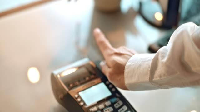 SLO MO sliding credit card through terminal and entering amount