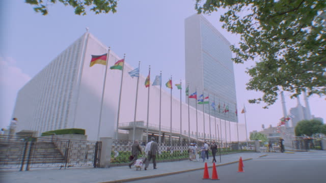 Slight low angle PAN of United Nations building + flags / people on sidewalk in foreground / NYC