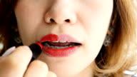 Slo Mo : Young woman applying lipstick