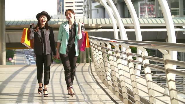 Slo mo: paar jonge vrouw gelukkig moment met boodschappentas na daar het geld besteden.
