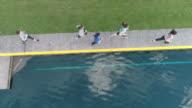 SloMo aerial view of women jogging next to a pond
