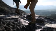 Slo-mo as hikers descend mountain ridge, cross creek