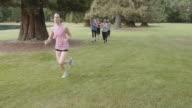 SloMo Group of athletic women jogging through a park