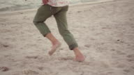 Slomo : Human legs running on the beach in water