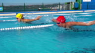 HD Slo-Mo: Two Young Women Swimming Butterfly Stroke Outdoors