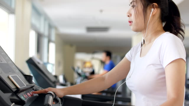 Slo-mo:Sport women running on treadmill cardio equipment