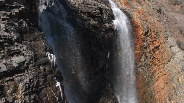 Slow flying view of waterfall with rainbow
