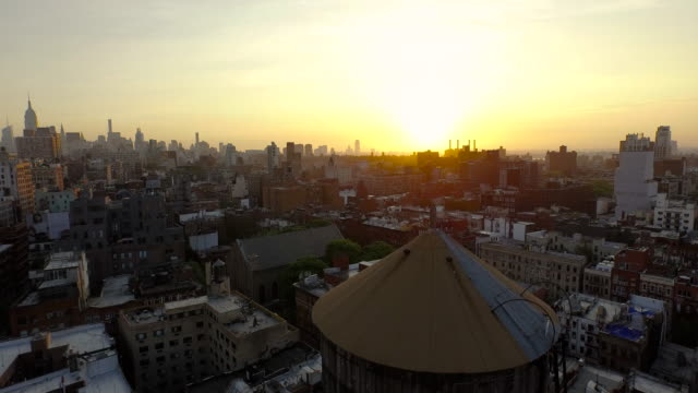 Slow glide up from behind water towers in Soho at sunrise to reveal city buildings