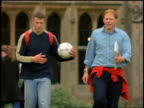 slow motion 2 male college students walking with soccer ball outdoors / England