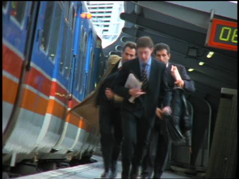 slow motion 3 businessmen rushing off passenger train at Waterloo train station / London