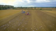Slow motion aerial drone footage of tractors ploughing and birds flying