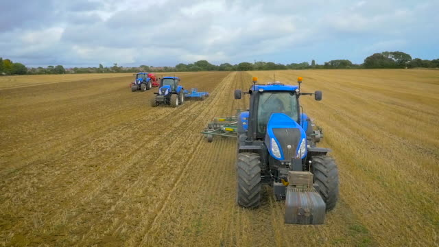 Slow motion aerial drone footage of tractors ploughing from the front