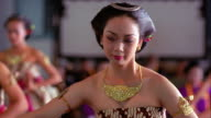 slow motion MS Asian woman in costume dancing / other dancers in background / Surakarta Palace, Java, Indonesia