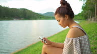 Slow motion Asian women using smartphone near river