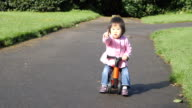 slow motion baby girl play scooter