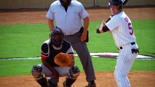 slow motion MS baseball player at bat hitting ball + running / catcher stands up next to umpire