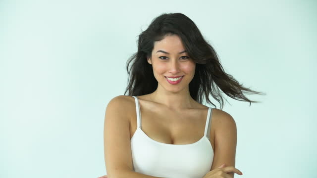 MS Slow Motion beautiful woman shaking her hair and smiling.