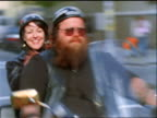slow motion PAN biker with woman on motorcycle driving on city street past camera