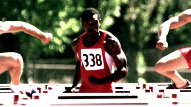 OVEREXPOSED SELECTIVE FOCUS slow motion Black man jumping hurdles in race on track