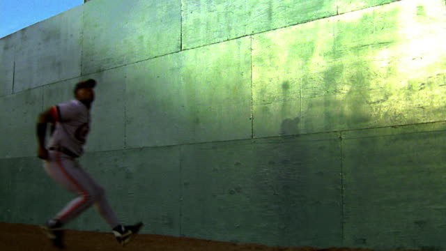 slow motion Black outfielder jumping + catching baseball against green wall