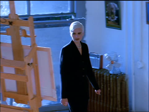 slow motion BLUE high angle PAN Gen X man in loft greeting woman + showing her paintings on easel + on wall