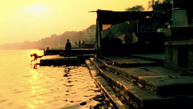 Slow motion boat point of view on Ganges River along silhouetted stairs (ghat) on bank with person in background / India