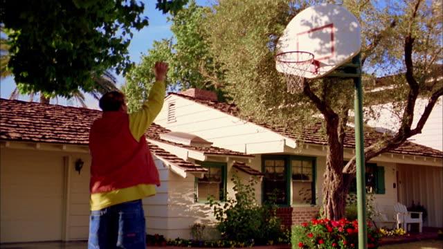 Slow motion boy shooting basket in hoop in driveway / Phoenix, Arizona