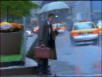 slow motion businessman with umbrella in rain waiting to cross NYC street