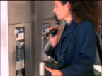 slow motion businesswoman picking up payphone + looking thru appointment book