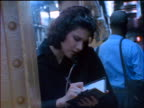 BLUE slow motion businesswoman talking on pay phone in subway station + writing in datebook / NYC
