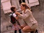 slow motion businesswoman talking to young schoolgirl / Paris