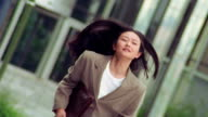 slow motion CANTED Asian businesswoman carrying briefcase running toward camera outdoors