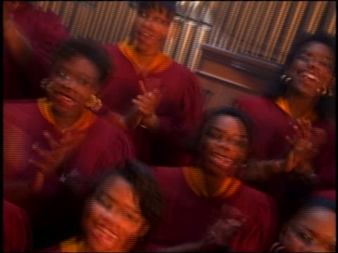 slow motion CANTED PAN Black gospel choir in robes singing + clapping in church
