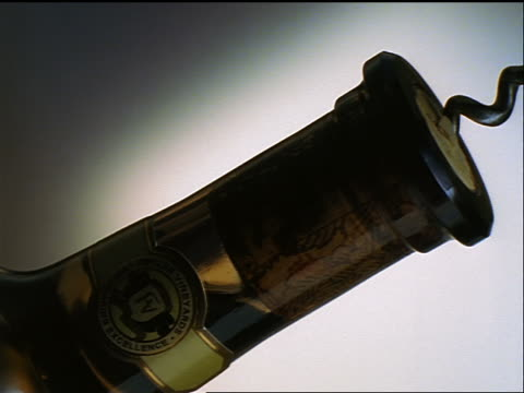 slow motion CANTED close up PAN cork being removed from wine bottle with gray background