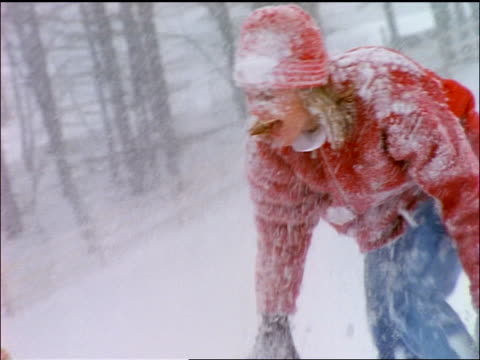 slow motion CANTED close up girl + mother having snowball fight in snowstorm