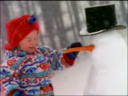 slow motion CANTED close up little girl knocking carrot out of snowman's face during snowstorm