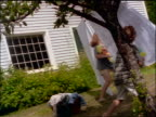 slow motion CANTED dolly shot children playing with large water guns by sheets on clothesline in backyard
